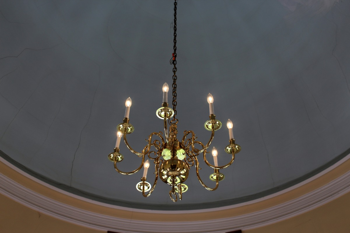 Luxe Gold Chandelier Set Against a Crumbling Domed Ceiling