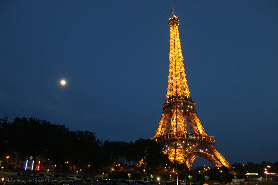 the-eiffel-tower-sparkling-at-night-with-moon-in-the-background